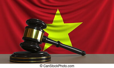 Judge's gavel and block against the flag of Vietnam....
