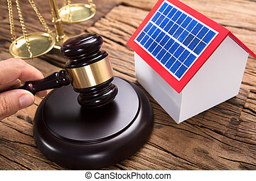 Judge's Hand Hitting Mallet By Solar Model Home On Table