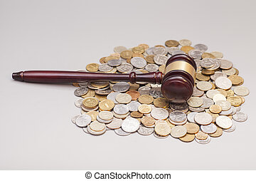 judges law gavel on pile of coins isolated on gray
