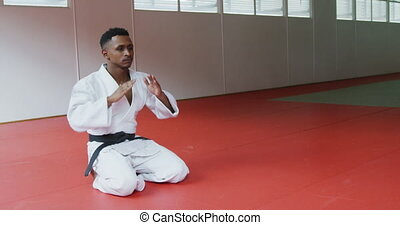 Judoka kneeling on the judo mat - SIde view of a teenage ...