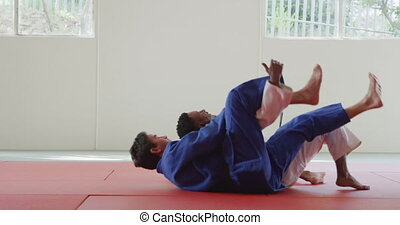 Judoka strangling his opponent on the judo mat - Side view ...