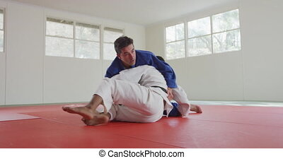 Judokas fighting and immobilizing on the ground - Front view...