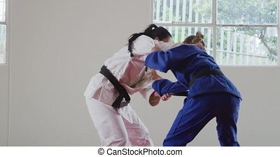 Side view of two teenage Caucasian and mixed race female judokas wearing blue and white judogi, practicing judo during a sparring in a gym in slow motion.