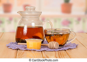 Jug and cup with hot tea and honey, on table
