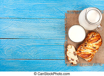 jug and glass of milk with a loaf of bread on a blue wooden background with copy space for your text. Top view
