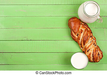 jug and glass of milk with a loaf of bread on a green wooden background with copy space for your text. Top view