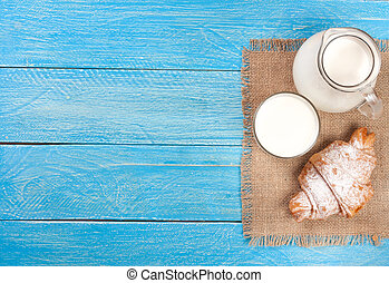 jug and glass of milk with croissants on a blue wooden background with copy space for your text. Top view