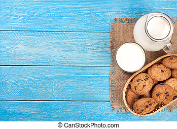 jug and glass of milk with oatmeal cookies on a blue wooden background with copy space for your text. Top view
