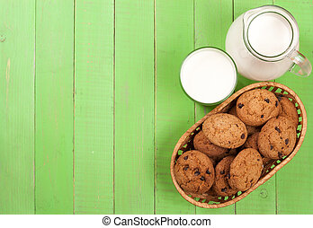 jug and glass of milk with oatmeal cookies on a green wooden background with copy space for your text. Top view
