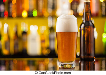 Jug of beer with bottle served on bar counter
