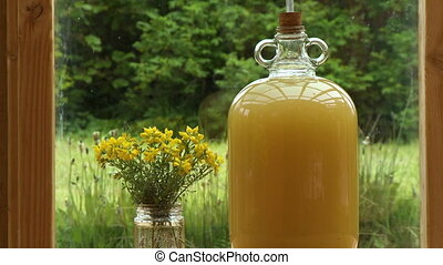 Jug of Juice and Yellow Flowers