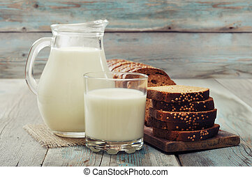 Jug of milk, glass and sliced bread on wooden background