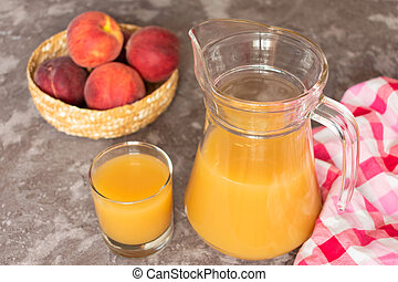 Jug of peach juice on a gray background. View from the top.
