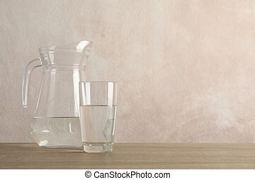 Jug with water and glass on wooden table, space for text