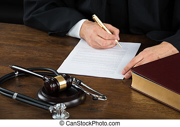 juge, écriture, sur, document, à, maillet, et, stéthoscope, bureau