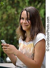 Jugendliche laechelt beim SMS-Schreiben - laechelnder...