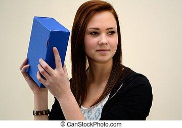 Jugendliche schuettelt blaue Schachtel - Teenager schuettelt...
