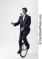 Juggling businessman on unicycle - Businessman riding a...