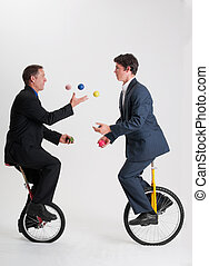 Juggling businessmen on unicycles - Two businessmen juggle...