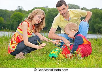 juguete, juegos, padres, niño, pasto o césped, se sienta