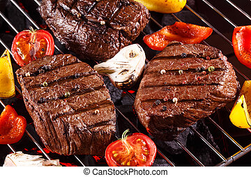 Beef steak on a barbecue grill with vegetables