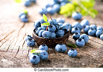 Juicy and fresh blueberries with green leaves in wooden bowl