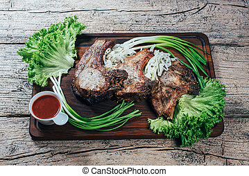 Juicy, appetizing pork steak is presented on a wooden board with green onions and lettuce leaves