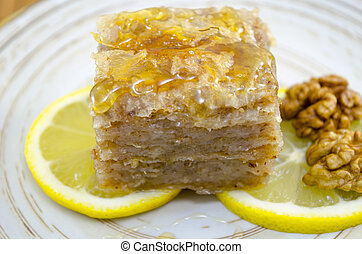 Juicy baklava on a plate decorated with lemon and walnuts