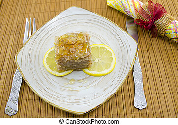 Juicy baklava on a plate decorated with lemon slices