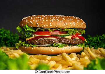 Juicy beef burger with cutlet, onion, vegetables, melted cheese, lettuce, sauce and topped sesame seeds. Isolated hamburger rotates on dark smoke background, close-up view