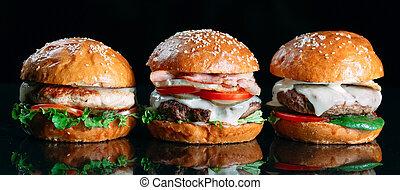 Juicy beef Burgers on a black background.