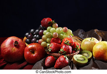 Juicy bright fruit, sprinkled with water, still life of seasonal fruits and berries, black background.