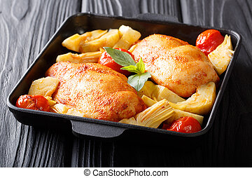 Juicy chicken breast with artichokes, tomatoes and basil close-up on a plate. horizontal