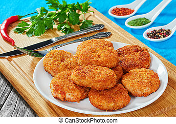juicy delicious chicken, pork, beef breaded cutlets on white...