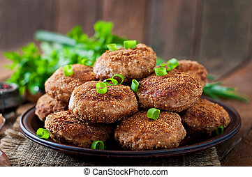 Juicy delicious meat cutlets on a wooden table in a rustic...