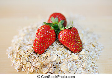 red strawberries on a pile of oat flakes