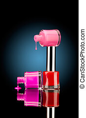 Three nail polish bottles of bright colors with juicy falling drops against black background.