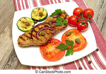 juicy grilled steak with vegetables on the plate on a wooden table