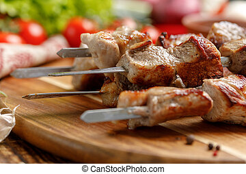 Juicy kebabs of pork lined on a decorative board. Meat cooked on open fire and fresh vegetables.