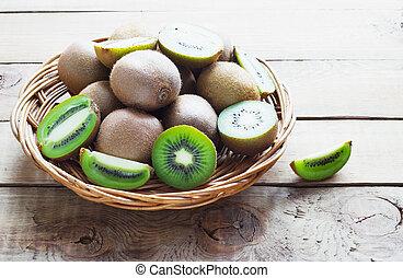 juicy kiwi fruit in a wicker basket on  wooden background
