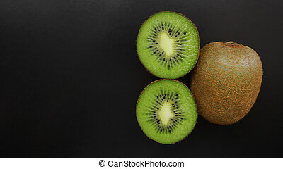 Juicy kiwi fruit on a black background, top view, copy space