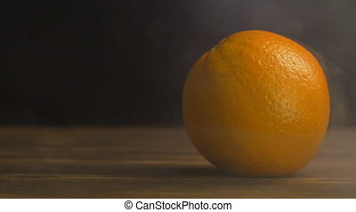Juicy orange on a black background in the smoke and...
