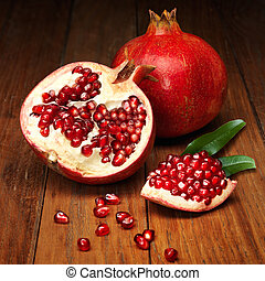 juicy pomegranate open on wood board
