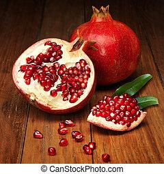 juicy pomegranate open on wood board