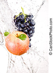 Juicy red apple and bunch of grapes in water splash isolated on white background