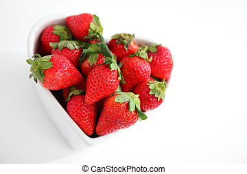 juicy red strawberries with Love heart bowl on white table...