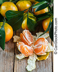 Juicy ripe tangerines with leaves on the table. Mandarin