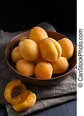 Juicy yellow riped apricot on dark background