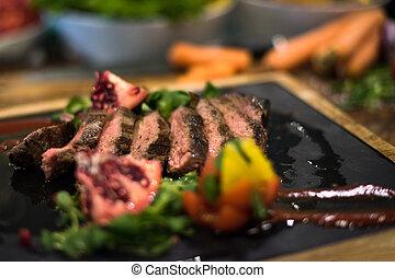 Juicy slices of grilled steak on wooden board