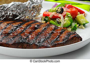 Juicy grilled steak served with a greek salad.